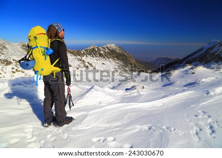 Mountain climber standing on snowy plateau above distant valley - stock photo