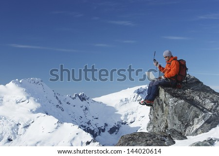 Mountain climber using laptop with walkie talkie on mountain peak against blue sky - stock photo