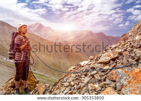 Mountain climber working with rope. Young woman belays her climbing partner with rope keeping it with both hands have protection gear helmet safety harness mountain landscape and rising sun background - stock photo