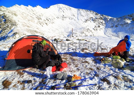 Mountain climbers prepare the camping site on snowy mountain
