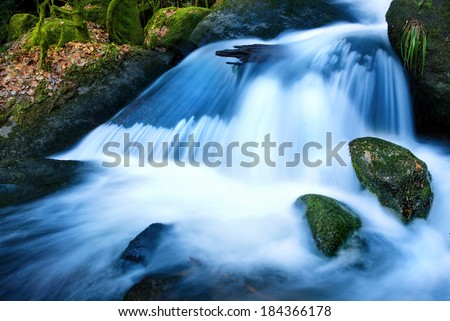 Mountain creek waterfalls with cool colors, long exposure for soft water look - stock photo