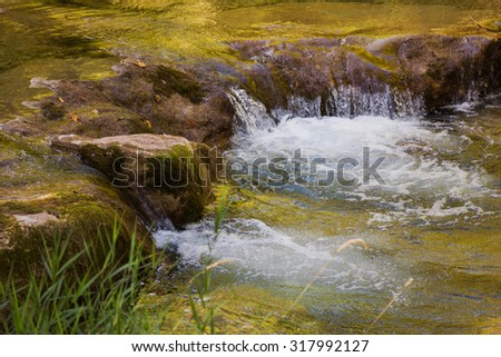 mountain creek with little cascade, golden water, autumnal scenery