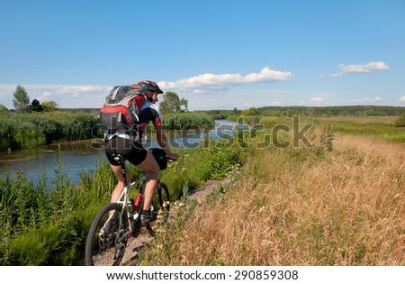 Mountain cyclist stands on the shore of the beautiful river. Ukraine.