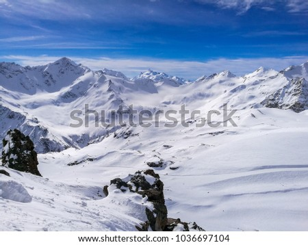 Mountain Elbrus, Caucasus Mountains in Russia and Georgia. Blue water, stones and snow in winter. Picturesque place, beautiful nature landscape. Tourism in winter. Blue sky, place for text.