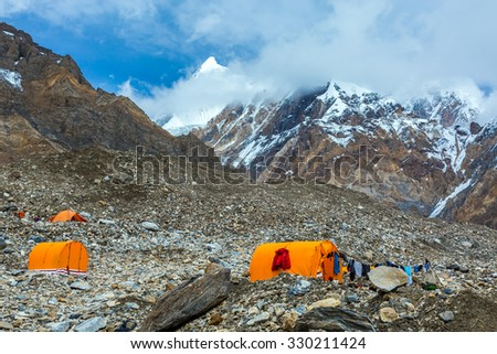 Mountain Expedition Camp Located on Giant Glacier Moraine Clothing Hanged on Tent for Drying after Rain - stock photo