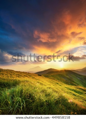 Mountain field during sunset. Beautiful natural landscape in the summer time