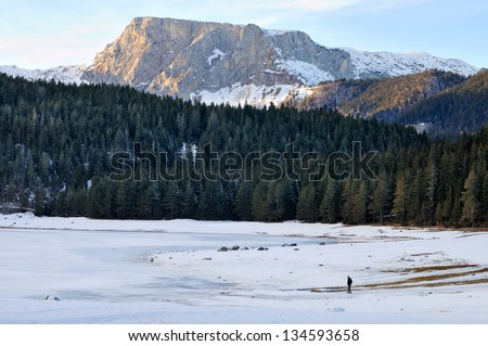Mountain forest, hill, frozen lake and man