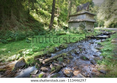 Mountain forest stream flows near the wooden house.