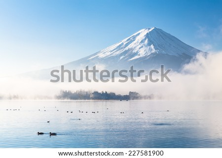 Mountain Fuji and Kawaguchiko lake with morning mist in autumn season - stock photo