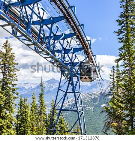 Mountain Gondola on a blue sky with snow peaked Rocky Mountains background (Banff. Alberta. Canada).  - stock photo