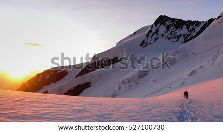 mountain guide and clients headed towards a summit in the Swiss Alps at sunrise