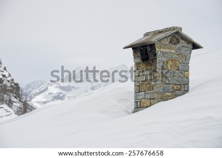 mountain house roof with smoking chimney on the deep white snow background - stock photo