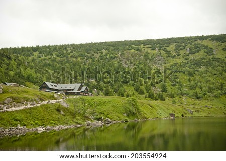 Mountain hut surrounded by hills, mountains and conifers during summer, cloudy day. - stock photo