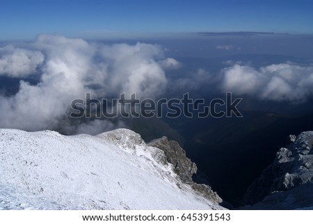 Mountain hut with snow and fog