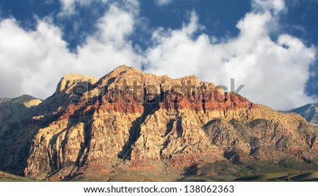 Mountain in Southwestern Nevada showing a geologic layer of iron oxide.