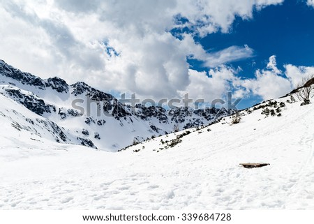Mountain inspirational beautiful landscape in winter day, valley in Tatra Mountains. Mountain ridge over blue sunny sky, Poland. - stock photo