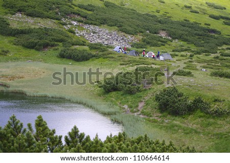 Mountain lake, and beside him leisure tourists and tents - stock photo