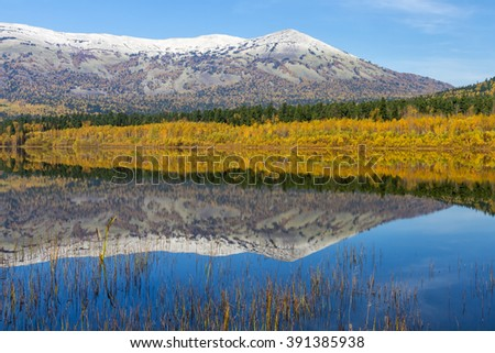 Mountain lake in autumn, reflections in water and the mountains with snow and trees in background