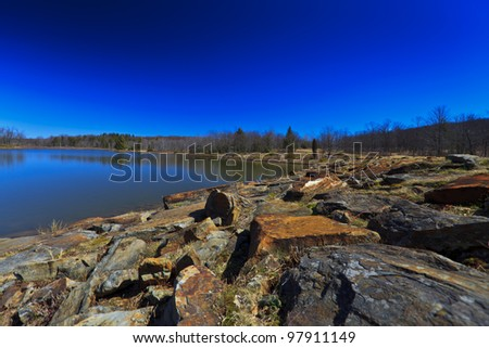 Mountain lake, old rocks and deep blue sky