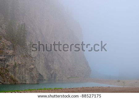 Mountain lake shrouded in morning fog - stock photo