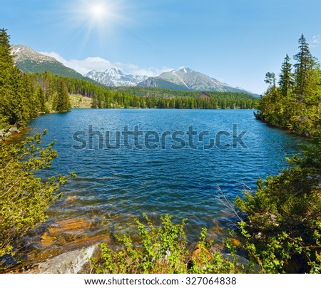 Mountain lake Strbske Pleso (Slovakia) spring view with sunshine in blue sky. - stock photo