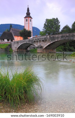Mountain lake with a stone church and bridge in the background
