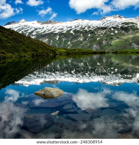 Mountain lake with clouds and blue sky - stock photo