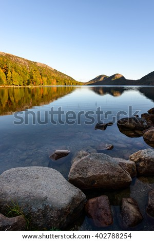 Mountain Lake with Colorful Trees Reflected in Water - stock photo