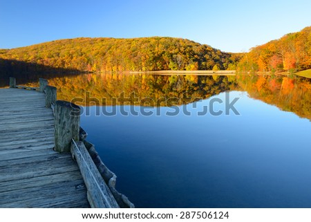 Mountain Lake with Dock Surrounded by Autumn Trees - stock photo