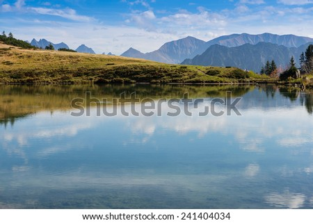 Mountain lake with reflection of the sky and clouds