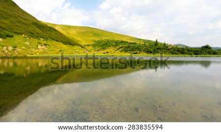mountain lake with stones on bottom, green hills reflected in water  - stock photo