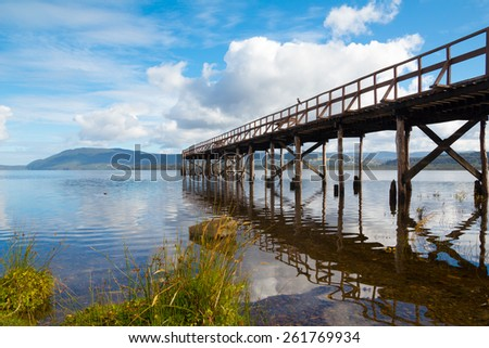 Mountain lake with wooden pier and bird on it at sunny day - stock photo