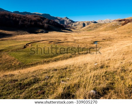 Mountain landscape in autumn with blue sky above.