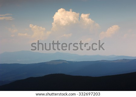 Mountain landscape in haze. Beautiful clouds in sky above mountain ridge. Stormy weather. Panorama