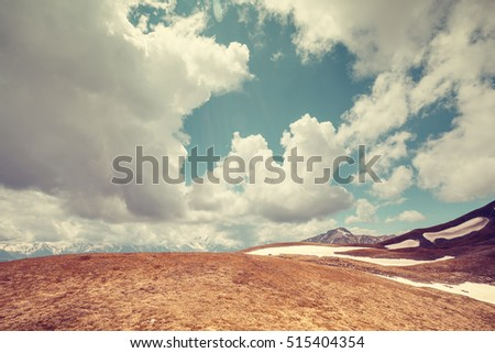 Mountain landscape in retro colors. Clouds over hill