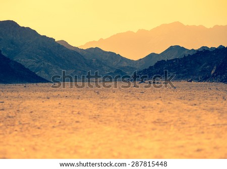 Mountain landscape in vibrant colors. Sunset at the hills in stone desert. Landscape with golden mountainous silhouette. Panoramic view of ridge mountains in Arabian desert. - stock photo