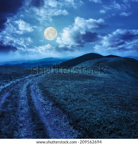 mountain landscape. path in valley  on the top of hillside at night in full moon light - stock photo