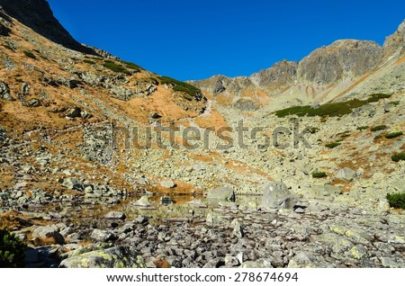 Mountain landscape. Picturesque view over lake, trail and rocky peaks in Tatra mountains in autumn season. - stock photo