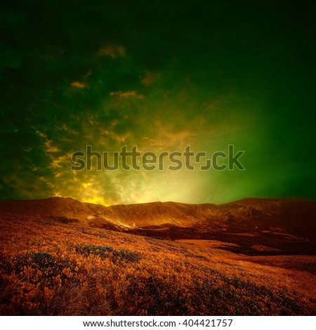 Mountain landscape toned with surreal colors, brown grass and green sky