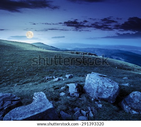 mountain landscape. valley with stones in grass on top of the hillside of mountain range at night in full moon dappled light  - stock photo