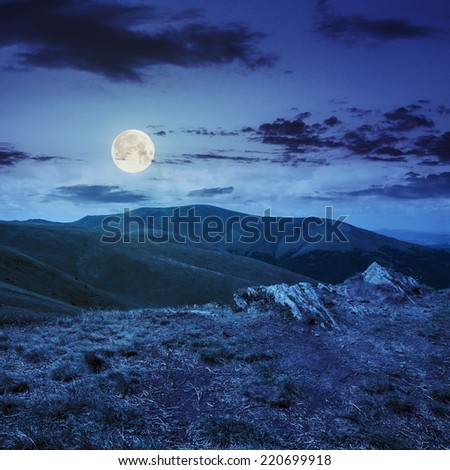 mountain landscape. valley with stones on the hillside. forest on the mountain under the beam of light falls on a clearing at the top of the hill. at night in full moon light - stock photo