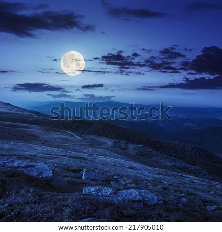 mountain landscape. valley with stones on the hillside. forest on the mountain under the full moon  light falls on a clearing at the top of the hill at night - stock photo