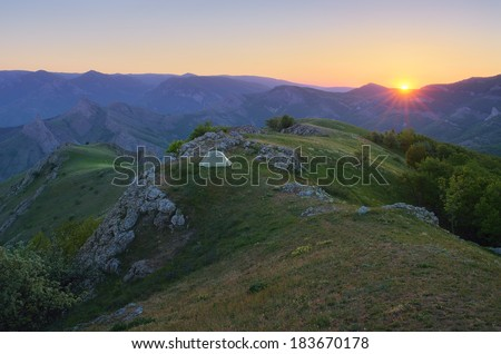 Mountain landscape with a beautiful sunset. Camping in the outdoors with a tent. The peninsula of Crimea, Ukraine, Europe - stock photo