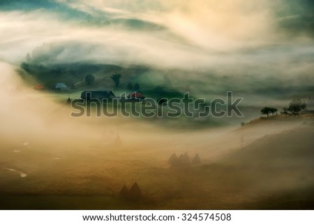 mountain landscape with autumn morning fog at sunrise - Fundatura Ponorului, Romania - stock photo