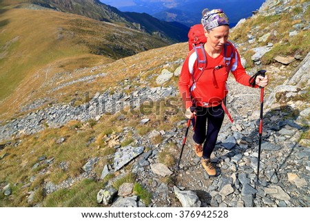 Mountain landscape with backpacker woman ascending a rocky trail - stock photo