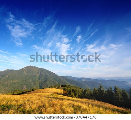 Mountain landscape with blue clouds over valley and Carpathian hills - stock photo