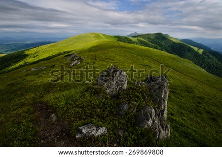 Mountain landscape with cloudy stormy sky and green sunny foreground grass - stock photo