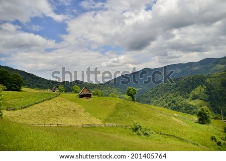 Mountain landscape with country house in romania/Country house in the mountains and green fields/Nice landscape with country house