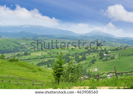 Mountain landscape with farmhouses and fence in the foreground on the background of mountain ranges and sky with clouds in summer