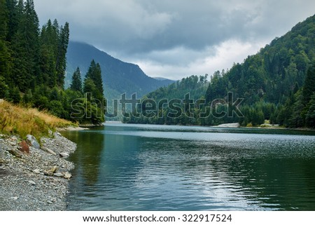 Mountain landscape with lake and pine forest in a cloudy day - stock photo